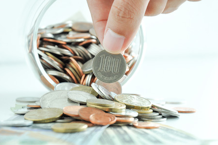 Hand picking up 100 Japanese yen (JPY) coin out of multi-currency pile of coins