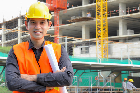 Asian engineer or foreman in front of construction site