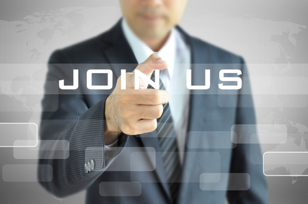 join hand: Businessman pointing to JOIN US sign on virtual screen Stock Photo