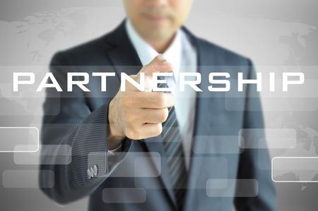 Businessman pointing to PARTNERSHIP word on virtual screen photo