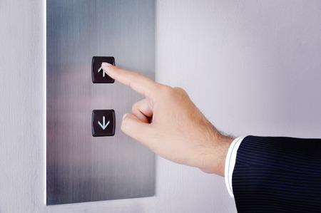 実業家の手サインを起こっているリフト コントロール パネルを押すと 写真素材