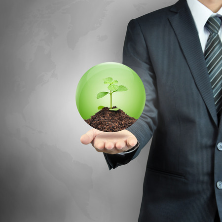 plant growth: Businessman carrying green sapling with soil inside the sphere - sustainable development & nature conservation concept