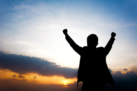 win win: Silhouette of man raising his arms - success, winning & accomplished concept