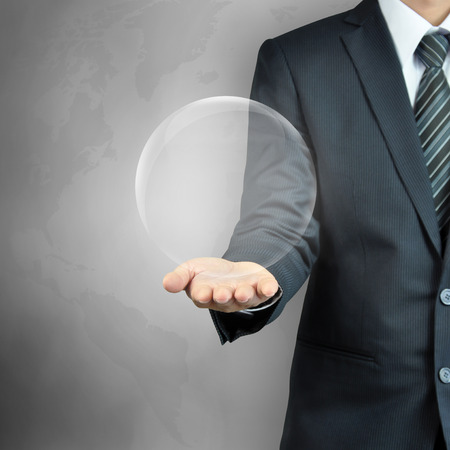businessman carrying a globe: Businessman hand carrying empty transparent ball or globe - can put your objects or texts inside