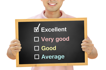 Tick mark in front of Excellent word on blackboard held by smiling man - evaluation & feedback concept photo