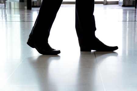 Businessman legs with black leather shoes walking on the floor photo