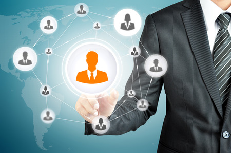 business leadership: Hand pointing to businessman icon in the middle that linked with each other as network - HR,HRM,MLM, teamwork & leadership concept Stock Photo