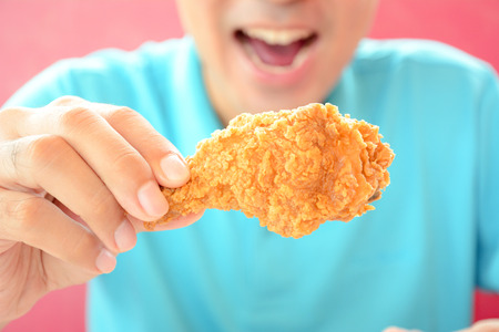A man with opening mouth about to eat deep fried chicken leg or drumstick photo