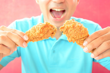 deep fried: A man with opening mouth about to eat deep fried chicken legs or drumsticks