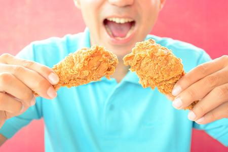 pollo frito: Un hombre con la apertura de la boca a punto de comer las piernas o muslos de pollo fritos Foto de archivo