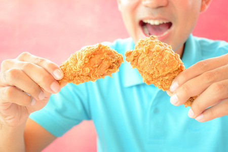 A man with opening mouth about to eat deep fried chicken legs or drumsticks photo