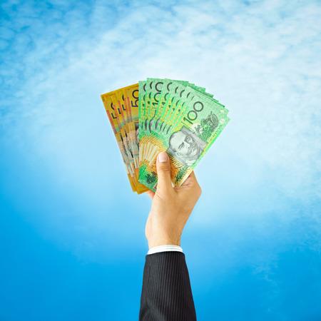 australian money: Money, Australia dollar (AUD) bills held by businessman hand on blue sky background Stock Photo