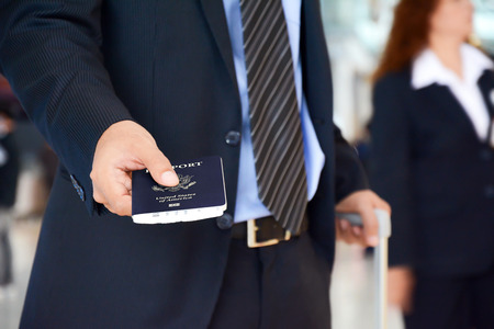 handing: Businessman showing U.S. passport - business trip, check in , boarding & airport immigration concept
