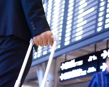 luggage travel: Hand of traveling businessman with baggage in front of airport timetable