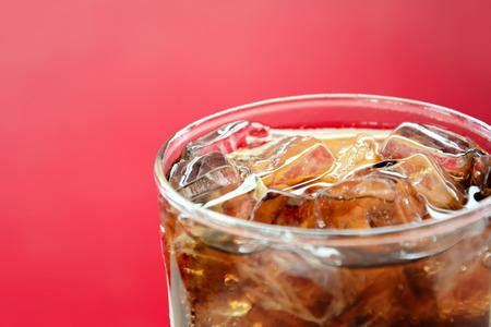 赤い背景の上の氷でコーラ清涼飲料のガラス 写真素材