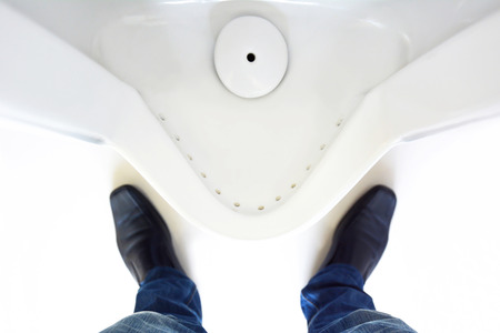 Top view of a man legs in front of urinal in men toilet photo