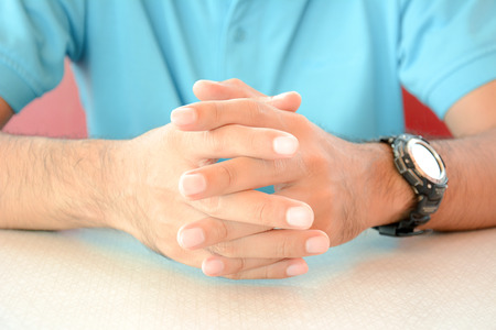 clasped: A man sitting with clasped hands on the table Stock Photo