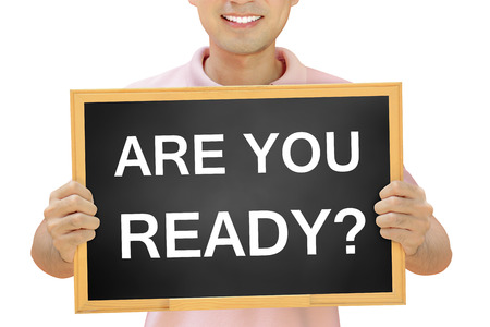 ARE YOU READY text on blackboard held by smiling man Imagens