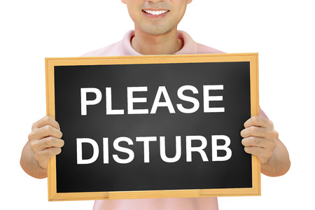 willingness: PLEASE DISTURB sign on blackboard held by smiling man - customer service concept