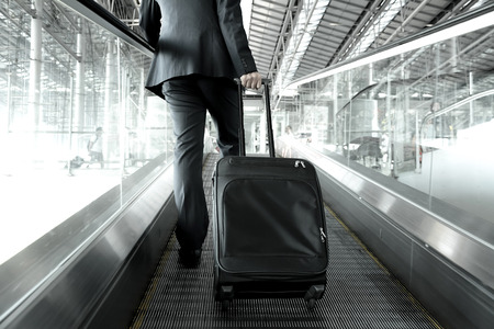 Businessman holding trolley bag going up on the escalator at the airport