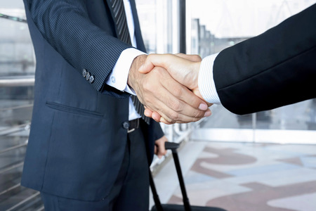 welcome symbol: Handshake of businessmen at the airport - business trip concept Stock Photo