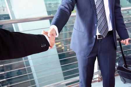 airport symbol: Handshake of businessmen at the airport - business trip concept Stock Photo