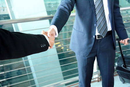business trip: Handshake of businessmen at the airport - business trip concept Stock Photo