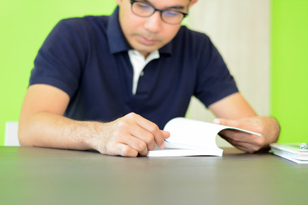 bookish: A man reading book on the table - studying & exam concept