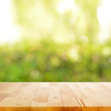 leuchtend: Holztischplatte auf Bokeh grünen Hintergrund