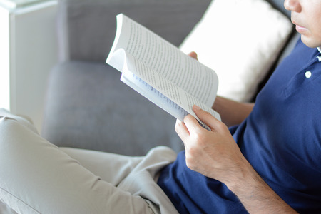 bookish: A man reading book while sitting on the couch