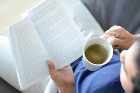 bookish: A man reading book with hot tea cup in another hand