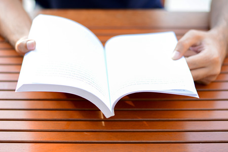 bookish: Hand opening book on the table - reading concept