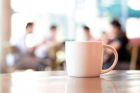 Coffee cup on the table with people in coffee shop as blur background Imagens