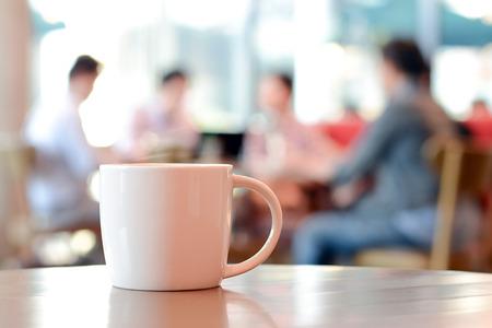 tazas de cafe: Taza de caf� sobre la mesa con la gente en la cafeter�a como fondo borroso Foto de archivo