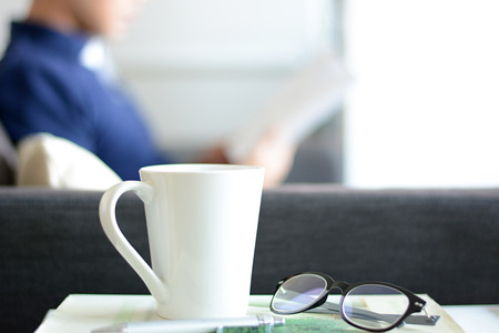 bookish: Coffee cup, eye glasses & pen over a book with blur background of a man reading book