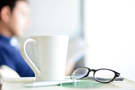 Tasse à café, verres et stylo yeux plus un livre avec flou fond d'un livre de lecture homme Banque d'images