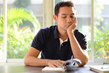 bookish: A man reading book - bored & moody concept