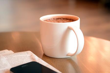 chocolate caliente: Taza de chocolate caliente en la mesa con papel de periódico y móvil al lado