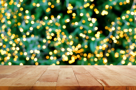 christmas display: Wood table top with bokeh background from decorative light on christmas tree - festive background concept Stock Photo