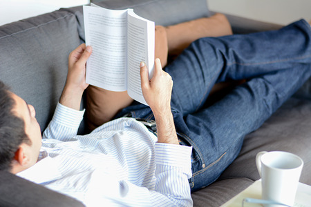 bookish: A man reading book while lying on the couch