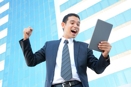 enthusiastic: Businessman raising his fist while looking at tablet pc - success, winning & overcome concepts