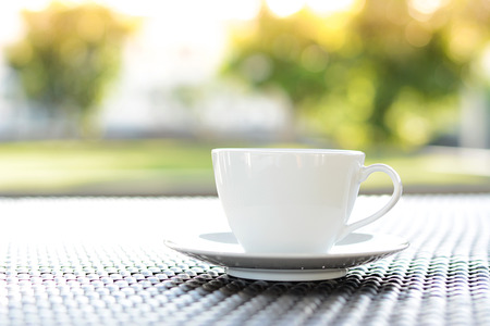 chill out: Coffee cup on the table with blurred green nature background - chill out concept Stock Photo