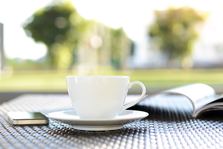 decaffeinated: Coffee cup with book on blurred green nature background - chill out concept