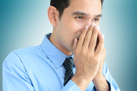 A man sneezing  without a tissue or cloth that may spread the disease