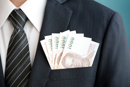 baht: Money in businessman suit pocket - Thai baht  (THB) currency Stock Photo