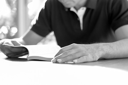 bookish: A man reading book on the table - monochrome effect
