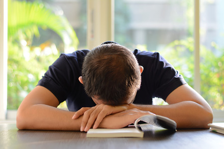 fatigued: Young man sleeping on the table with book opened, weary & tired of reading (studying)