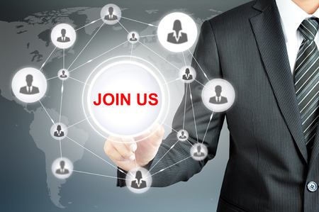 partake: Businessman hand pointing on JOIN US sign on virtual screen with human icons linked as network