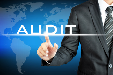 validation: Businessman touching AUDIT sign on virtual screen