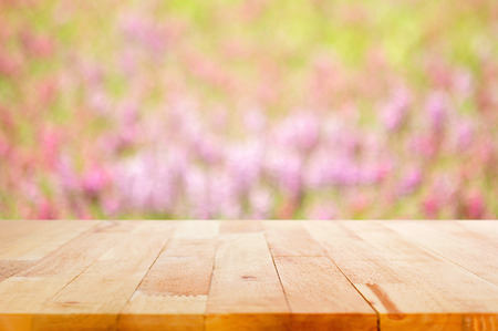 flowers field: Wood table top on blur flower garden background
